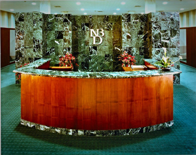 Luxurious commercial loan area in a major bank by interior designer Steven C. Adamko, with custom wool carpeting, exotic veneer and Verde green marble