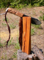 Camp knife splitting wood.