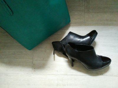 black high-heeled booties and jade tote bag