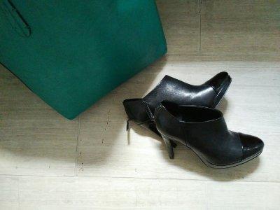 black high-heeled booties and jade tote bag