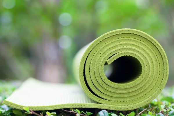 Photo of a green yoga mat rolled up and resting on the grass. More greenery is in the background.