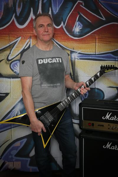 Martin Wilson stood with guitar