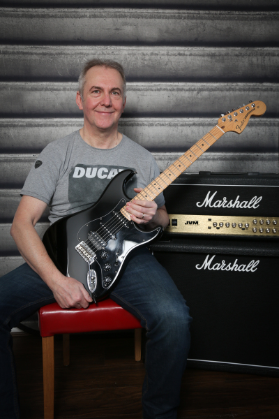 Martin Wilson sat with guitar next to Marshall amplifier