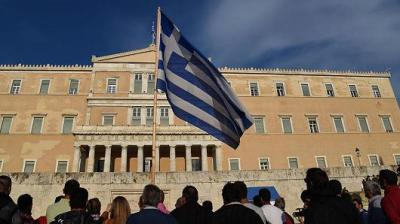 "alt=""Greece Flag in front of crowd & building"""