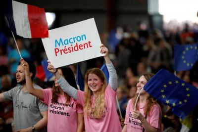 "alt=""Macron, Le Pen exchange May Day blows across Paris"""