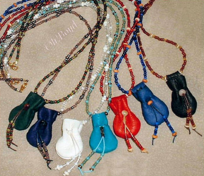 Tiny deerskin pouch as focal piece of graceful bead necklace.
