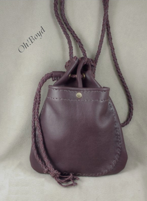 A drawstring pouch purse features lots of sturdy hand stitching and braiding. Front view.