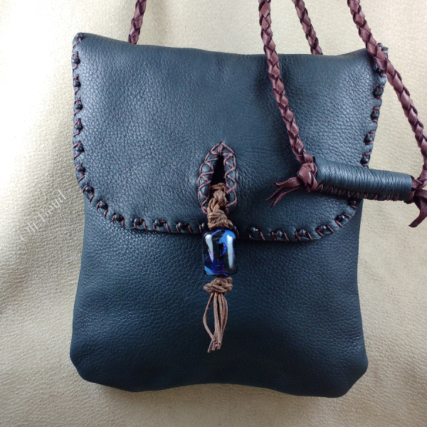 A flap closure deerskin purse with adjustable strap.