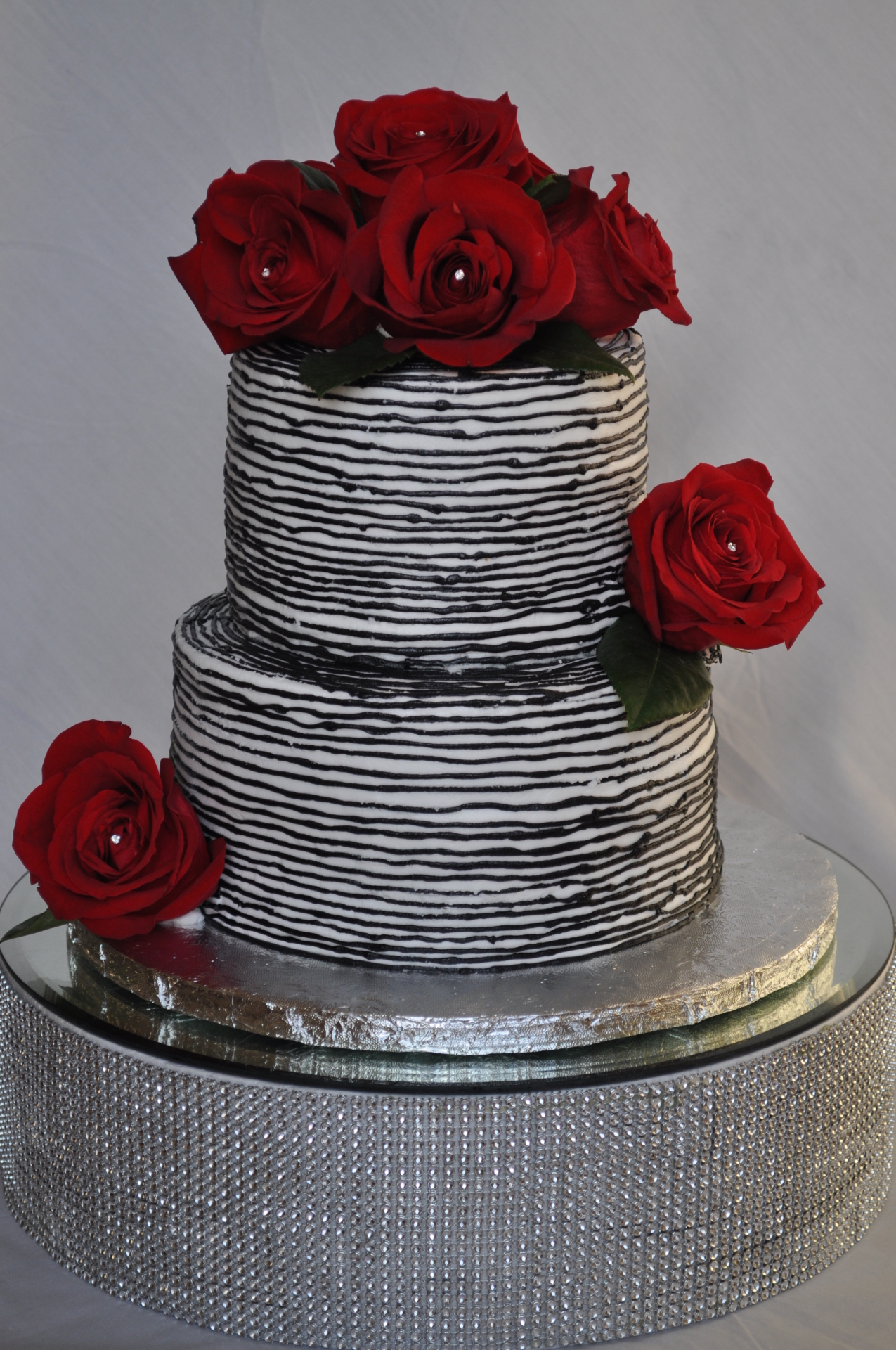 Black and White buttercream lined pattern topped with fresh red roses