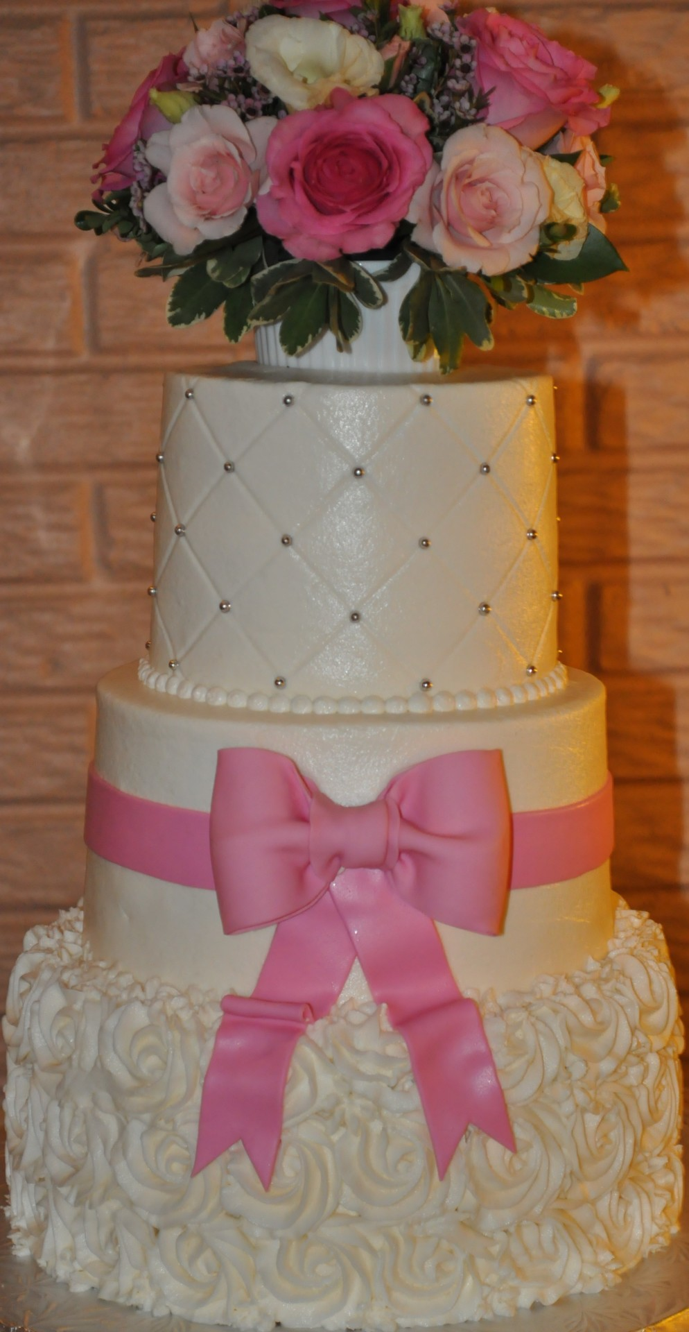 White rosettes with pink bow and fresh flower topper