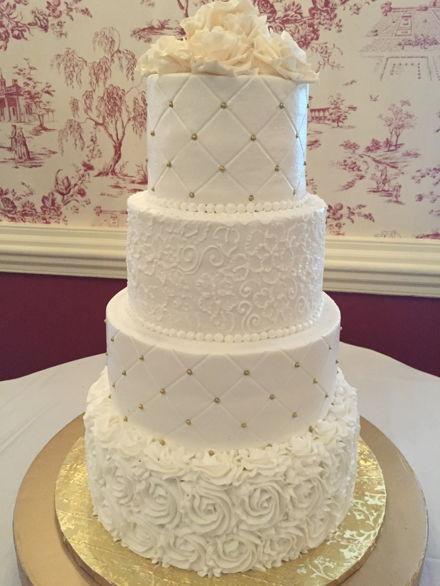 White rosettes and brush embroidary topped with white sugar roses