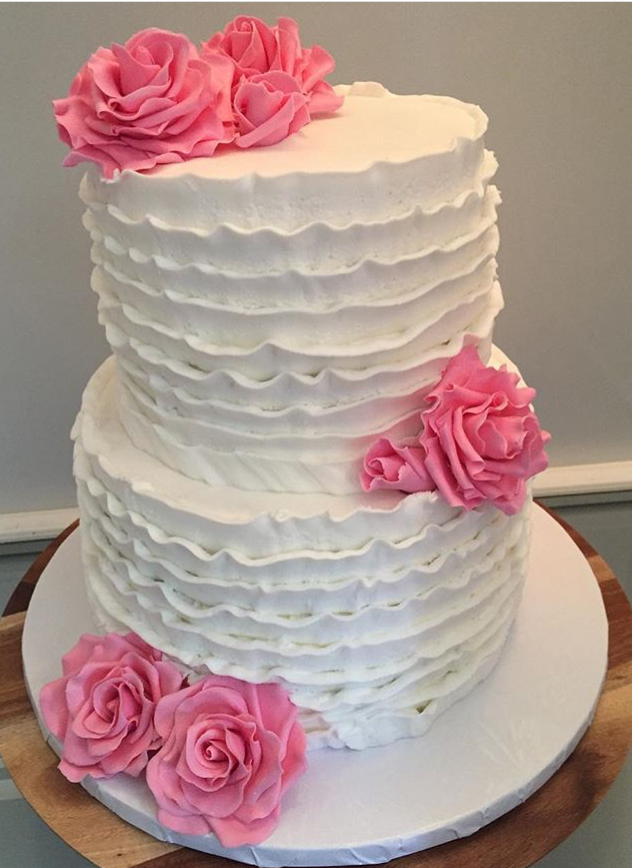 White icing ruffles and pink sugar flowers 2 tier