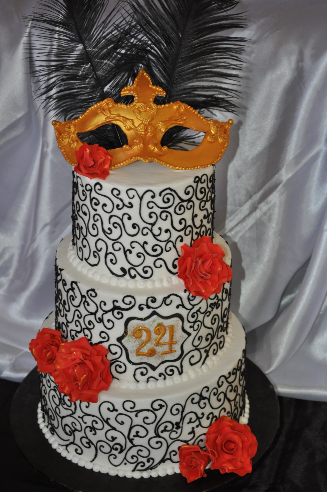 Gold mask black scrolls feathers cake