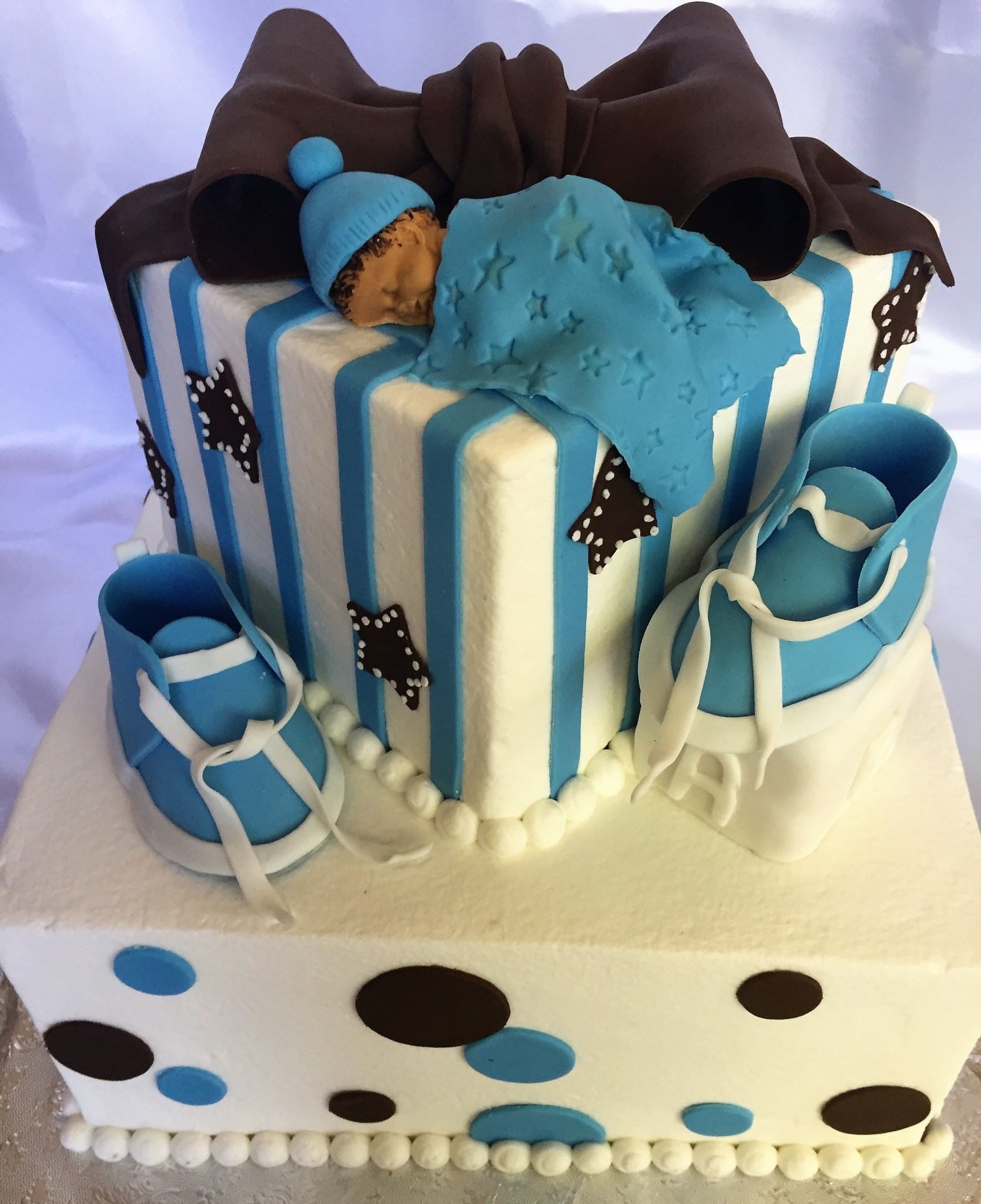 Square tiered cake with shoes,baby,bow and block
