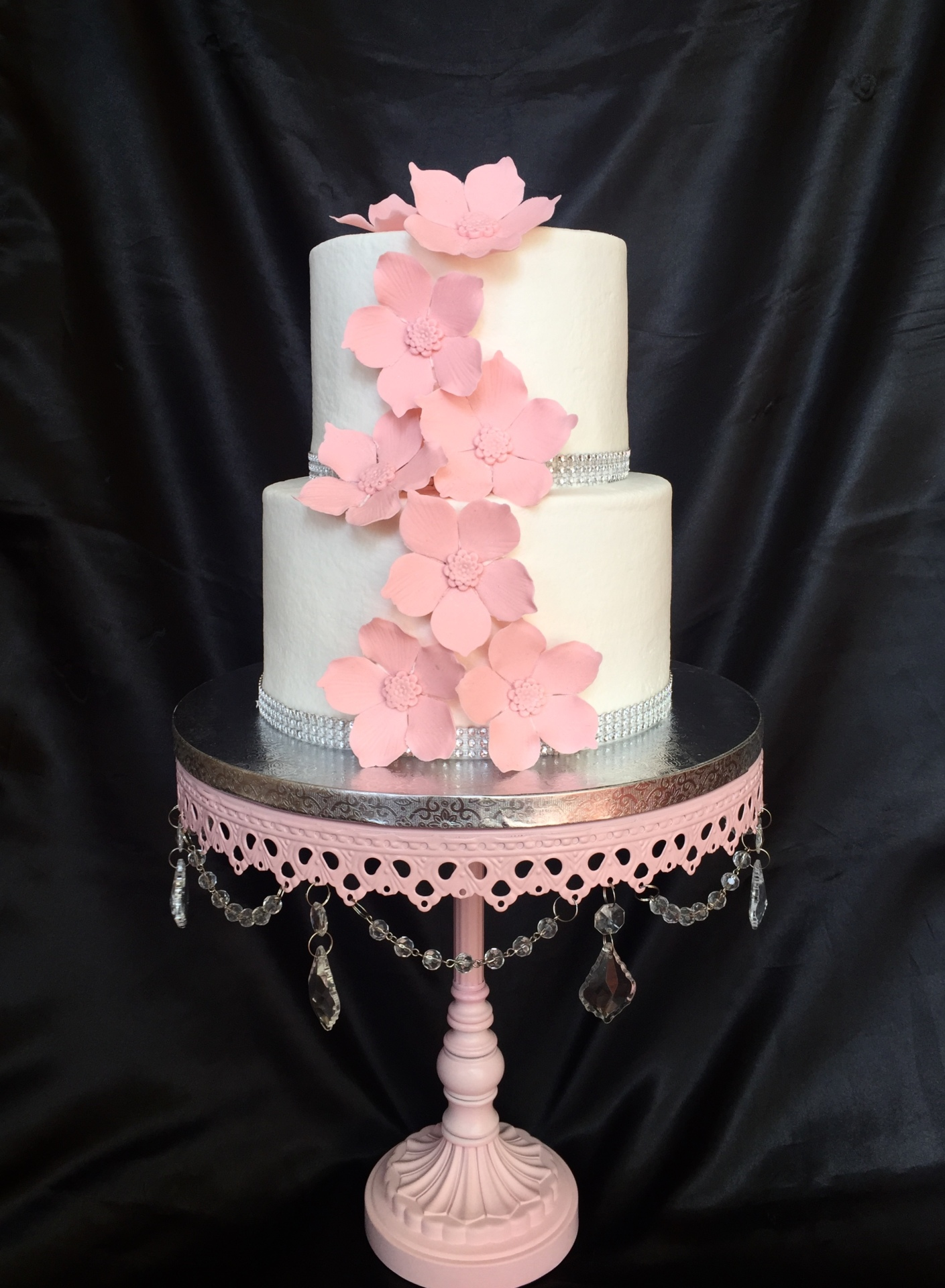 Buttercream with pink cascading fantasy sugar flowers.