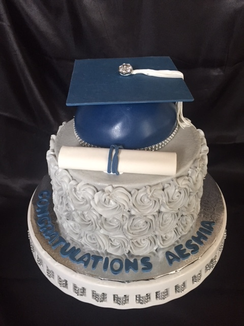 Navy hat and gray rosettes grad cake