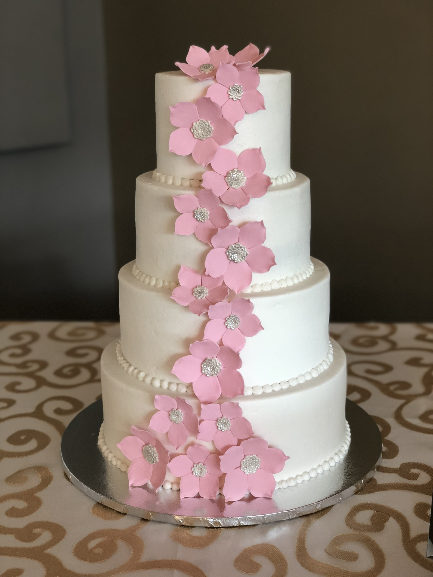 Buttercream cake with cascading pink sugar flowers