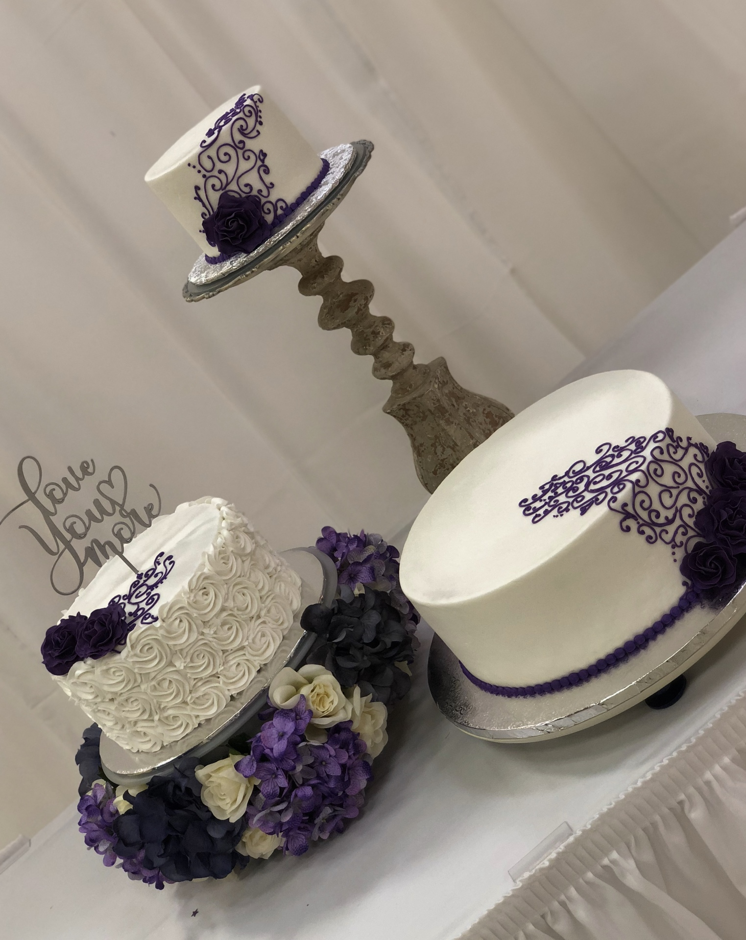 Cascading tiers with purple scrolls and sugar roses