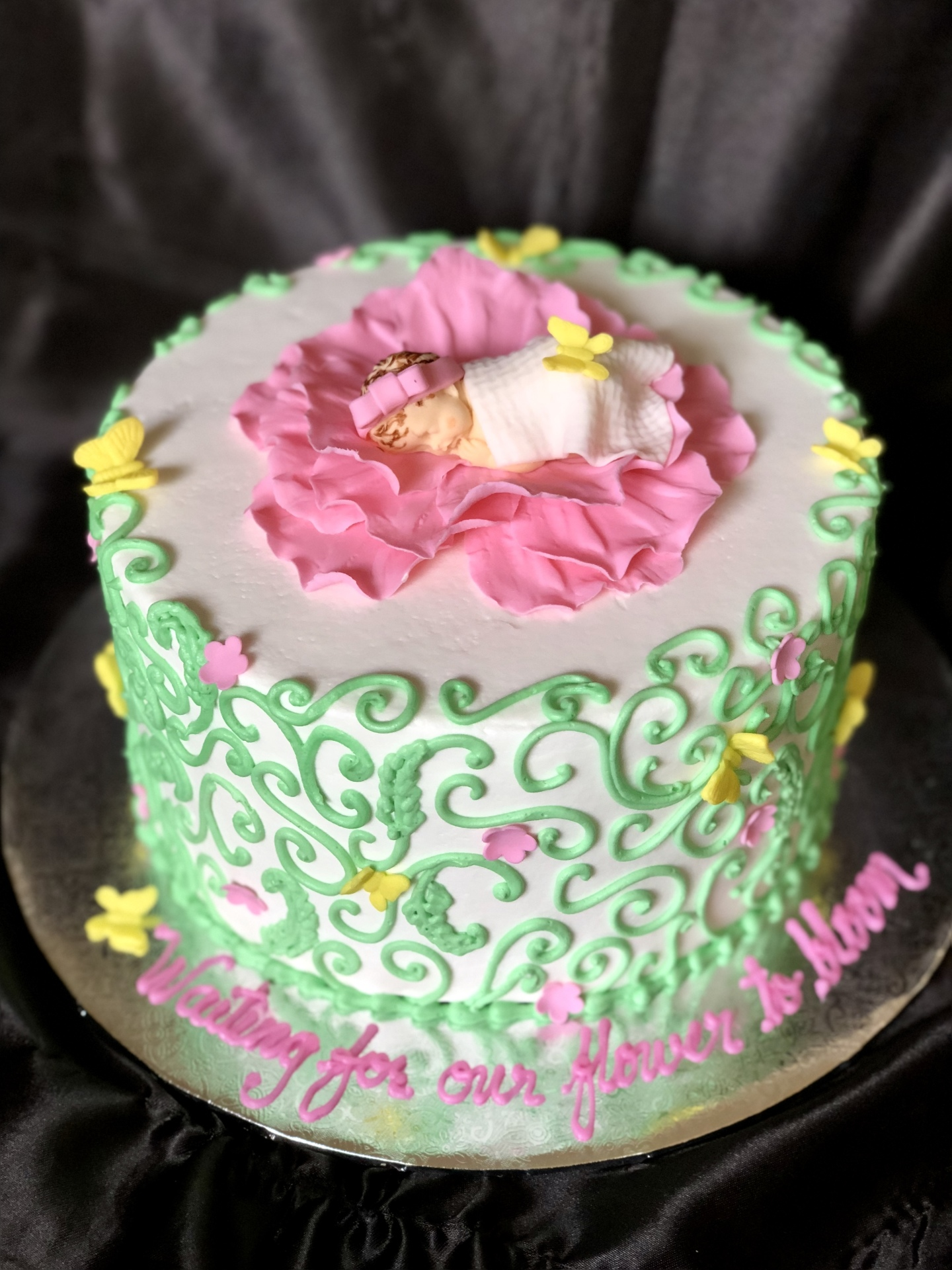 Fondant baby in pink flowers and green scrolls