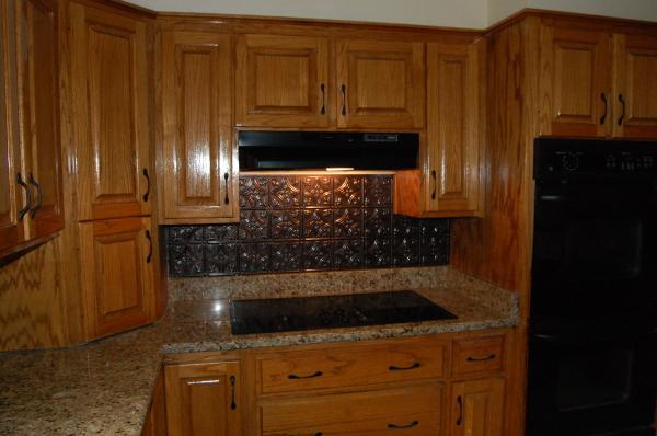 Venetian Gold Counter Tops, Copper Backsplash, Black Appliances