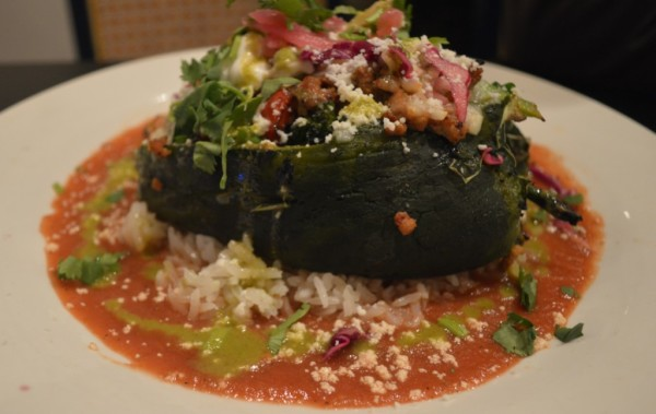 Charred Poblano Pepper stuffed with Cuban-Style Ground Pork, Veggies, Cheese Served on a bed of White Rice, Mild Totato Sauce Topped with Cabbage Salad, Avocado Puree and Sour Cream