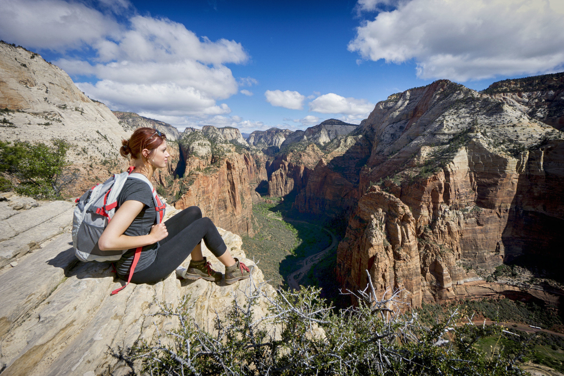 Girlfriend sitting on the side of a cliff overlooking zion national park from the top of angel's landing