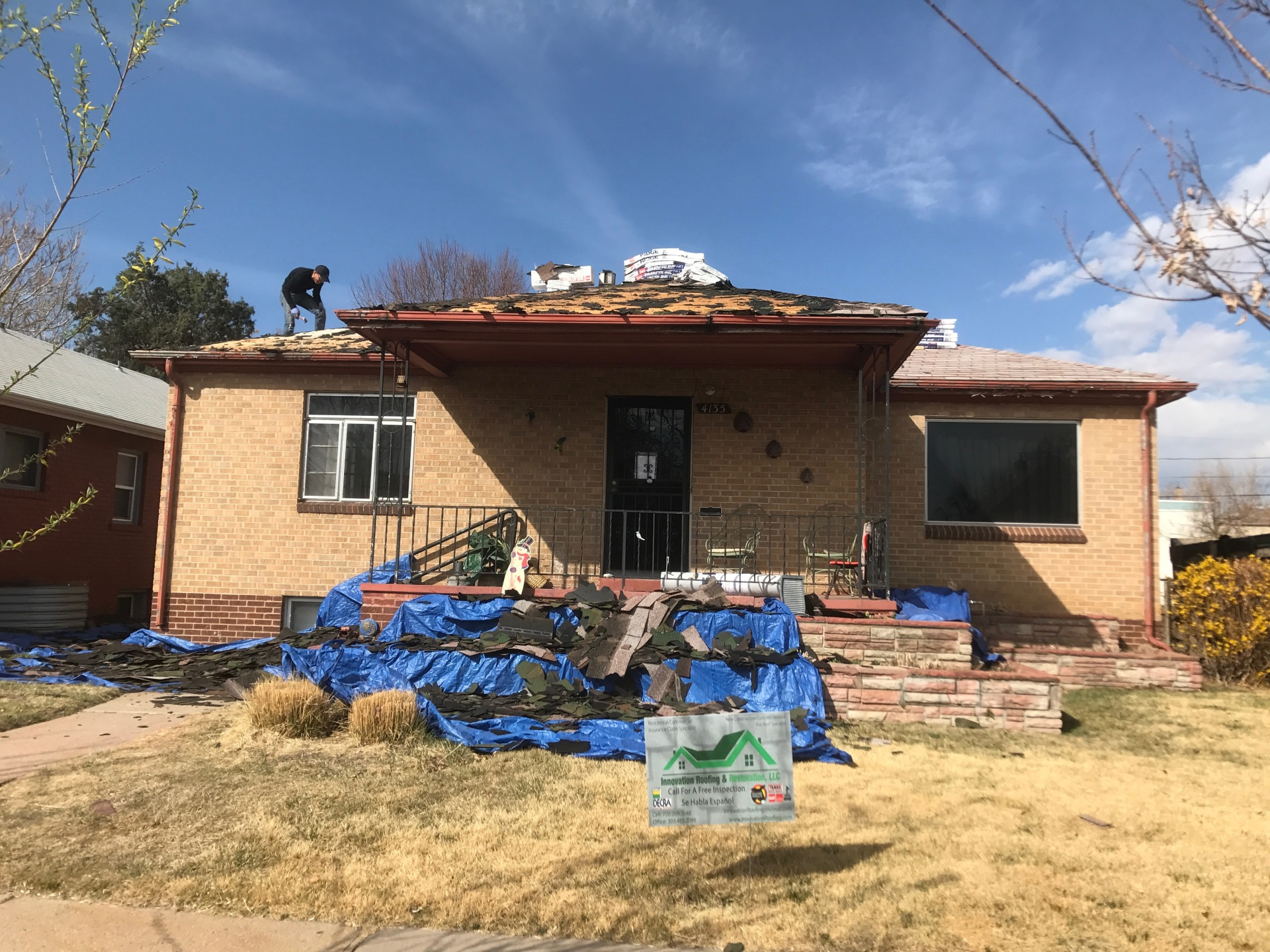 tearing off old roofing system damaged by hail