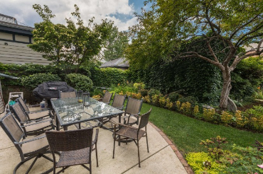 Lush garden with outdoor seating and gas grill