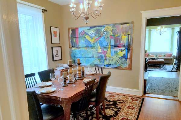 Chicago Guest House on Newport. Formal dining room with original artwork on walls