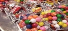 Bright, old-time candy shop with bulk bins selling sweets from jelly beans to dark chocolate.