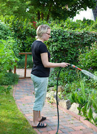 Woman watering flower bed with a hose