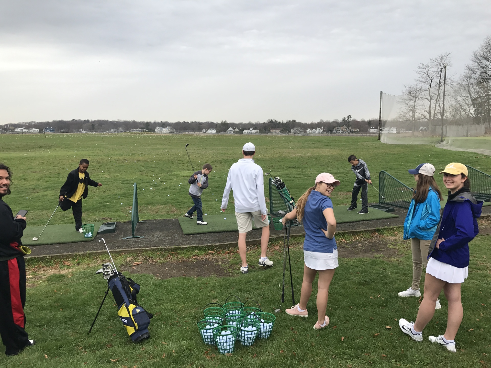 The Golf to Give Team and kids on the driving range