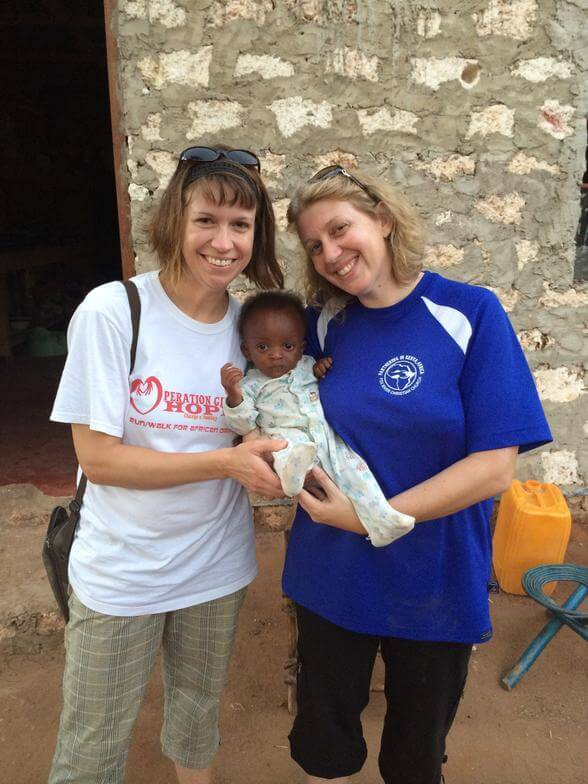 Carrie and volunteer holding baby