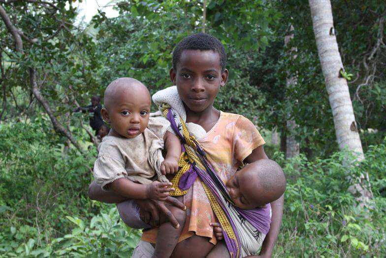 young village girl carrying two babies