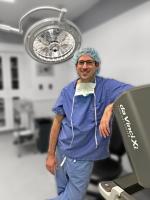 Dr. Michael Sutker standing near the da Vinci surgical system's console.