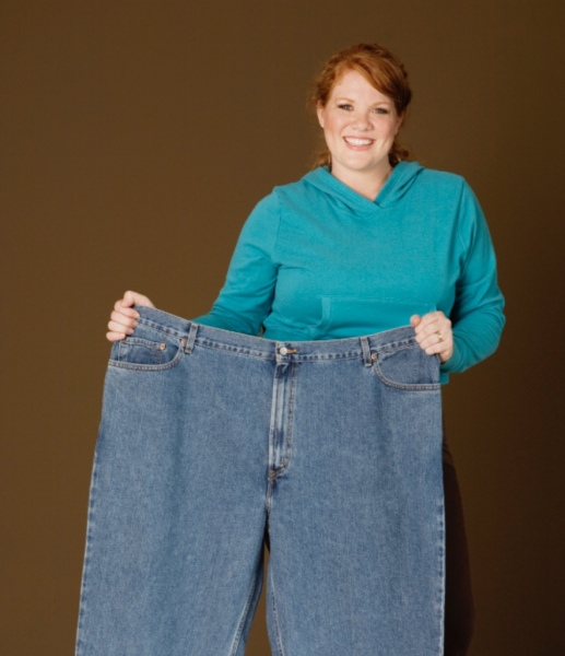 woman holding up large pair of pants after weight loss success
