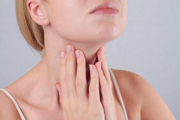 woman feeling her neck for a thyroid mass