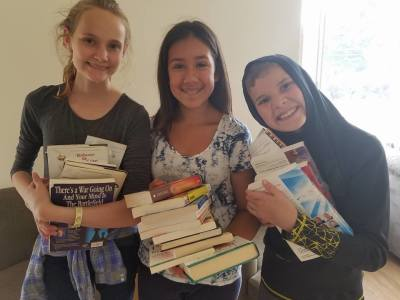 Our younger volunteers gathering books for our families
