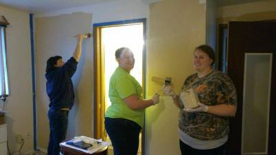 Volunteers adding a fresh coat of paint to one of our residences