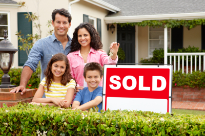 family standing by home sold sign