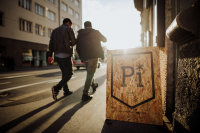 Powder institute sign, standing infant of a busy street in innsbruck. Guys walking past into the sunset.