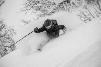 female skier wearing Helly Hansen jacket, skiing in deep powder snow.