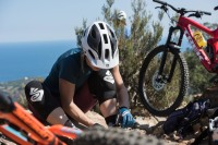 Enduro mountain biker wearing a sweet protection helmet and mons royale clothing fixing a puncture.