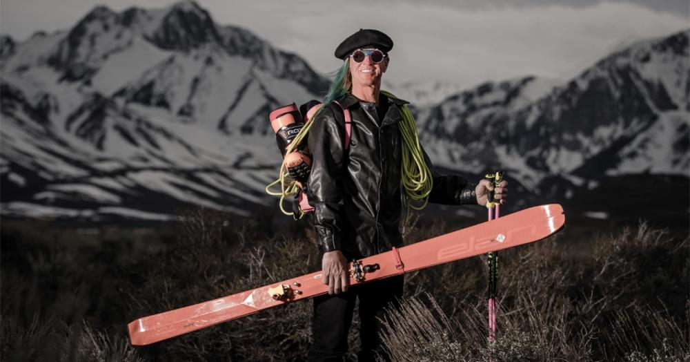 Glen Place, famous freeride skier, holding Elan freeride ski and climbing rope, stood infant of snow covered mountains.