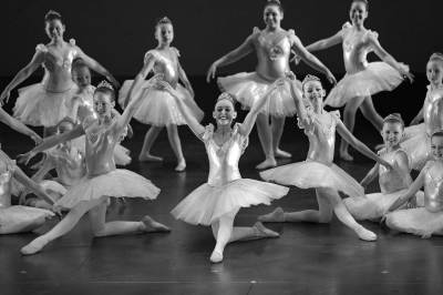 Young ballerinas in tutus in pose on stage