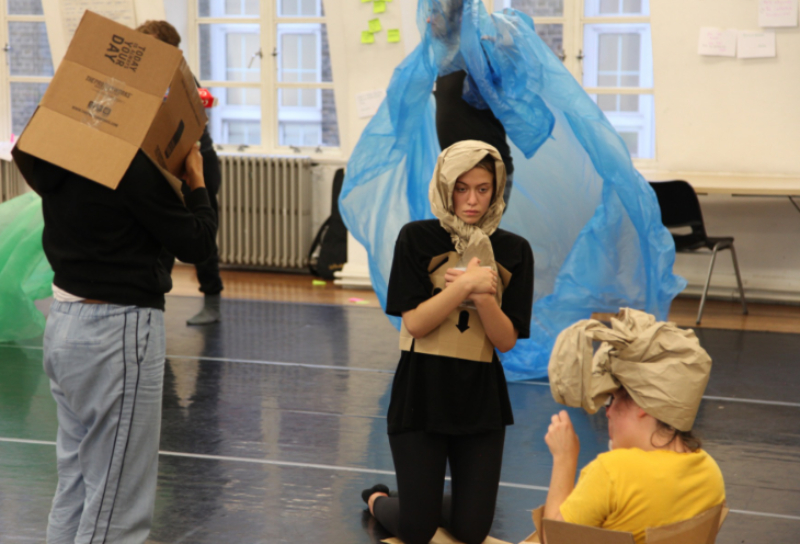 Tashi Baiguerra and Beth Watson play with cardboard and paper in a physical improvisation exercise.