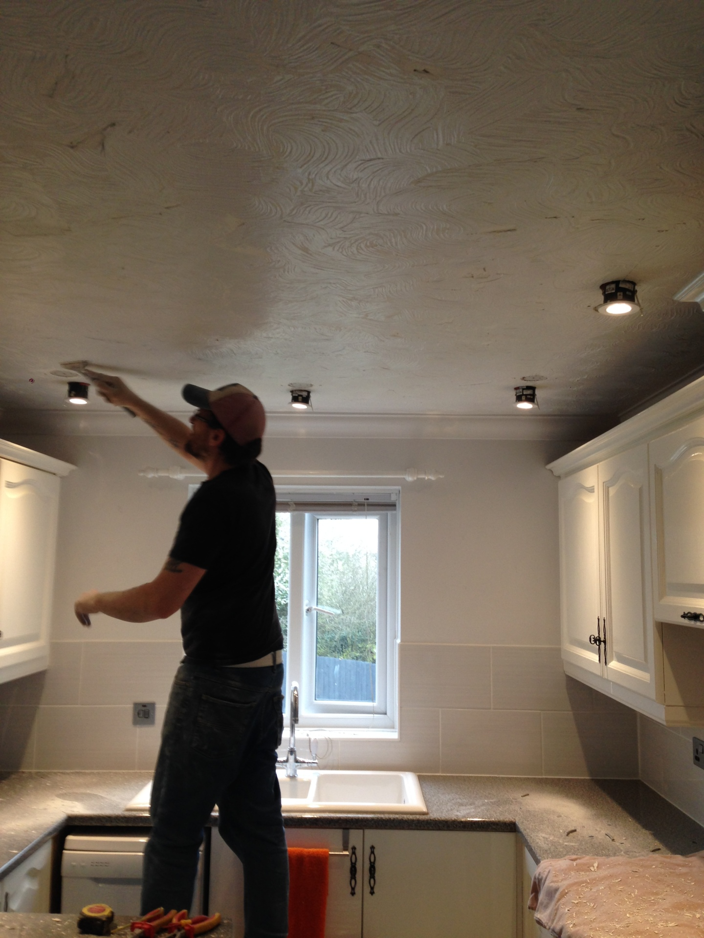Electrician at Scarlett Electrical helping install spotlights in a kitchen refurb