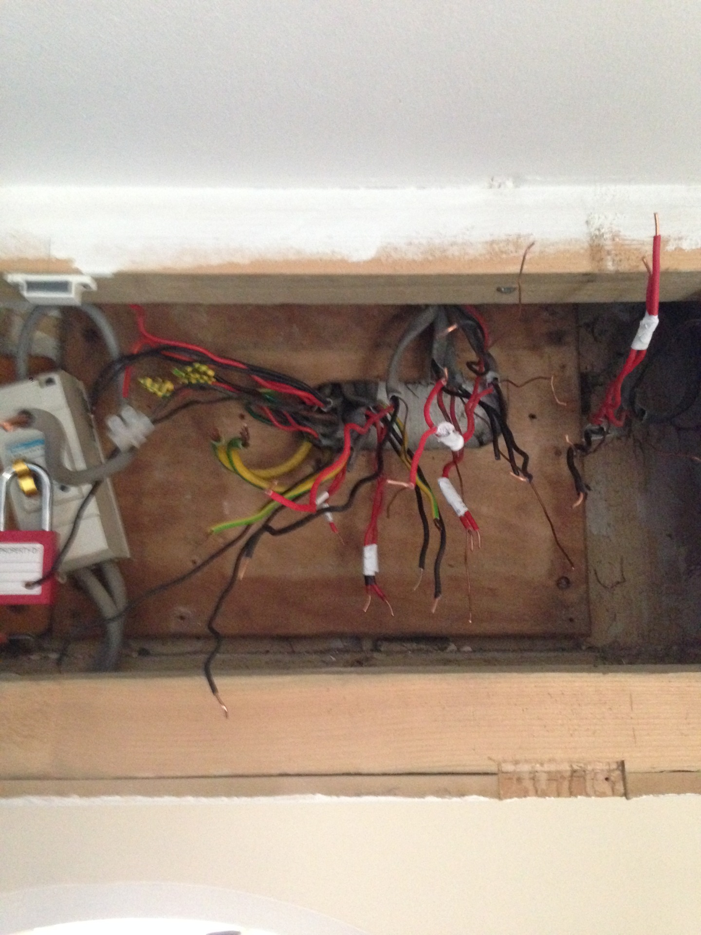 Exposed wires during a consumer unit changeover, note the correct locking off of the mains supply