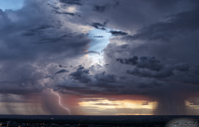 Two monsoon thunderstorms develop over Albuquerque, New Mexico at sunset, one with a cloud-to-ground lightning strike caught on camera.