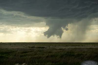 A funnel cloud and fragments of scud clouds develop with a parent supercell over southeastern Colorado.